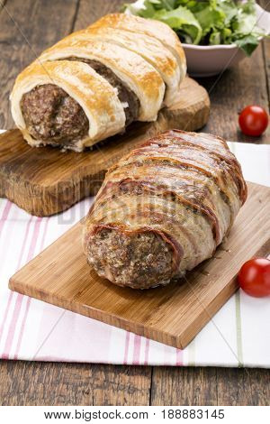 Minced meatloaf wrapped in bacon on wooden table
