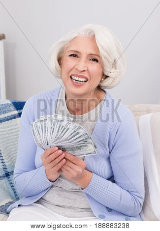 Elderly woman holding much money in her hands she won in lottery. Beautiful woman smiling for camera and sitting on sofa or couch.