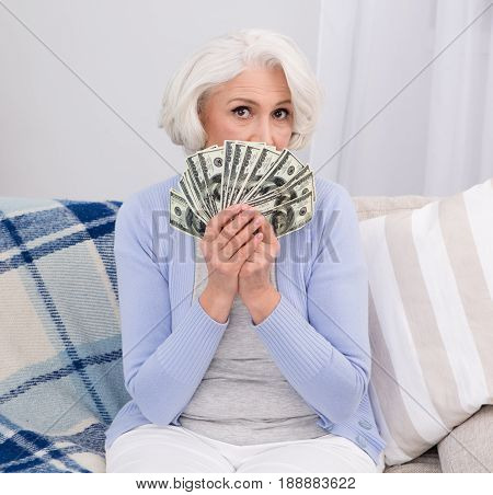Elderly woman thinking how to distribute inheritance. Elderly woman holding much money in her hands while sitting on sofa or couch.