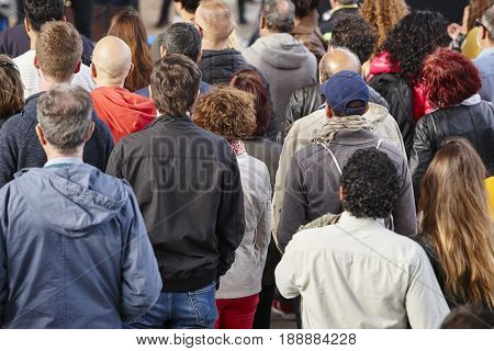 Group of people listening on the street. Urban crowded background.