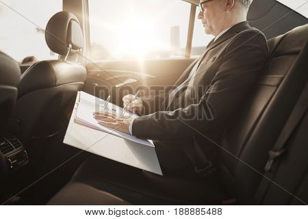 transport, business trip, paperwork and people concept - senior businessman signing papers with pen and driving on car back seat