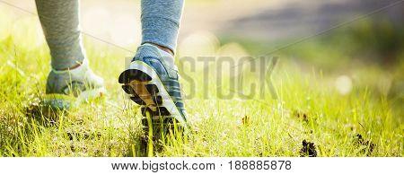 Closeup on shoe of athlete runner woman feet running on park. Sport concept