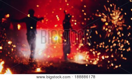 Blurred fireworks on beach at night fire-show performance, telephoto