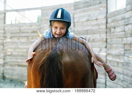 Little girl on horseback. The concept of teaching children riding