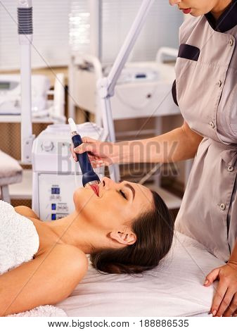 Ultrasonic facial treatment on ultrasound face machine. Woman has electric lift medical massage spa salon. Stimulation muscles by microcurrent therapy. Modern methods of rejuvenation.