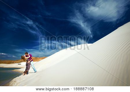 Embracing lovers on romantic travel honeymoon vacation summer holidays romance. Young happy lovers, caucasian woman and man embracing outdoors