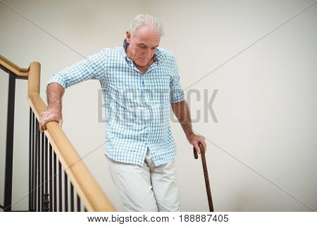 Senior man climbing downstairs with walking stick at home