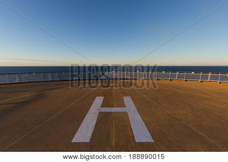 helicopter landing place on a ship deck on sea with blue sky in the morning sun