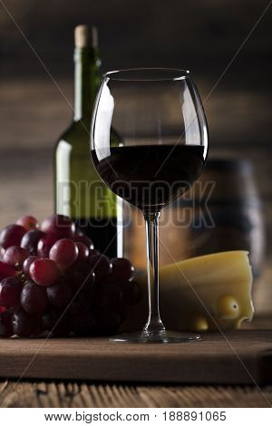 Glass of red wine, cheese and grapes on old wooden table. Old wooden background.