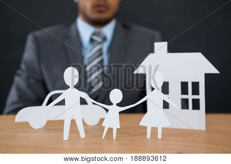 Close-up of paper cut out family chain with car and house at desk