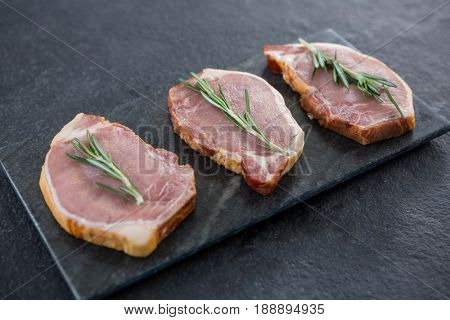 Sirloin chops and rosemary herb on slate plate against black background