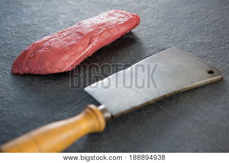 Beef steak and cleaver against black background