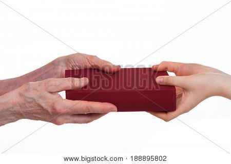 Hands of an elderly person and a child's hands hold a book, isolated on a white background. A symbolic image of the transmission of experience from generation to generation.