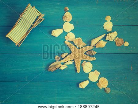 Airplane of seashells and starfish with a deckchair on a blue wooden background travel or vacation concept