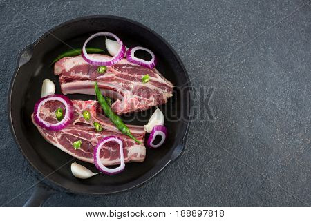 Blade chop and chopped chillies and onions in frying pan against black background