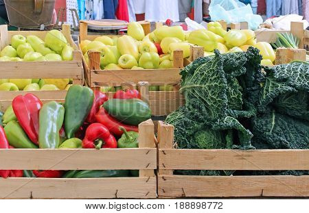 Fresh organic vegetables in wooden crates on market stall