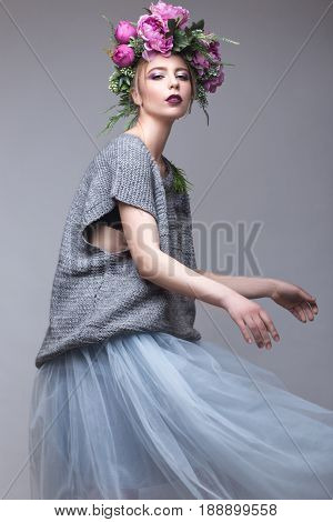 Beautiful girl with flowers on her head in fashion clothes posing against the background in the studio. Beauty Style