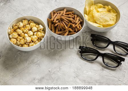 film whatching party with glasses, crumbs, chips and pop corn on stone background