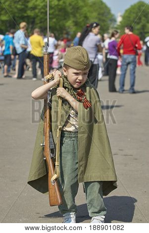 MOSCOW, MAY 9, 2010: Young boy in green USSR WWII uniform with soviet rifle on celebration of Great victory 65th anniversary in Gorky Park garden. USSR  9 May Great Victory parade day