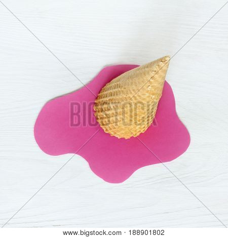 Inverted wafer cone with melted pink ice-cream cut from paper top view / Concept summer heat