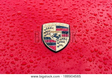 BERLIN - MAY 13 2017: Hood emblem of sports car Porsche in raindrops on the red background. Exhibition