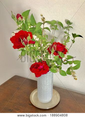 A bouquet of flowers in a vase. Red roses in white vase.