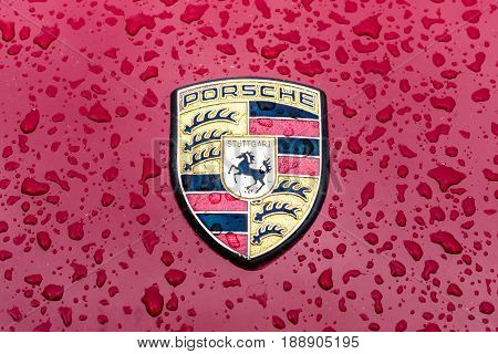 BERLIN - MAY 13 2017: Hood emblem of sports car Porsche in raindrops on the burgundy background. Exhibition