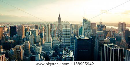 Great view of the New York City (NYC) skyline with a few high buildings and sun in the background.