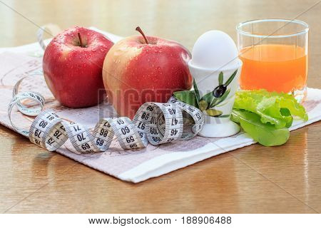 Apples, Egg, Salad, Ruler And Multivitamin Juice In Glass