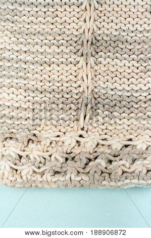 Sweater or scarf fabric texture large knitting. Knitted jersey background with a relief pattern. Braids in knitting . Wool hand- machine .