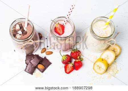 Set of milkshake in jars. Banana chocolate and strawberry milkshakes with nuts and coconut on white. Summer dessert. Healthy food. Top view.