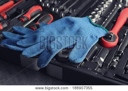Gloves and toolbox on grey table