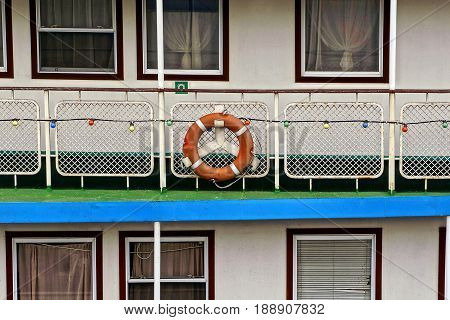 Part of a pleasure boat with a life ring on the railing