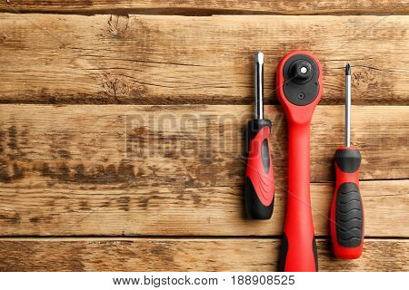Ratchet and screwdrivers on wooden background