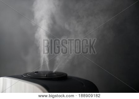 Technology for health. The humidifier evaporates steam in the room against the backdrop of the black wall.