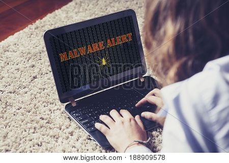 Woman using a laptop with malware alert notification in the screen.