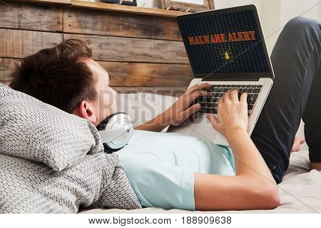Malware alert in a laptop computer being used by man at home.