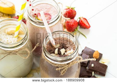 Set of milkshake in jars. Banana chocolate and strawberry milkshakes with nuts and coconut. Close up