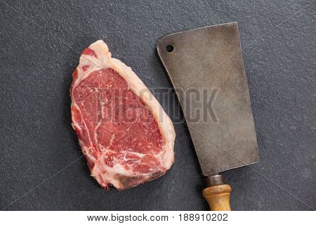 Close-up of sirloin chop and cleaver against black background