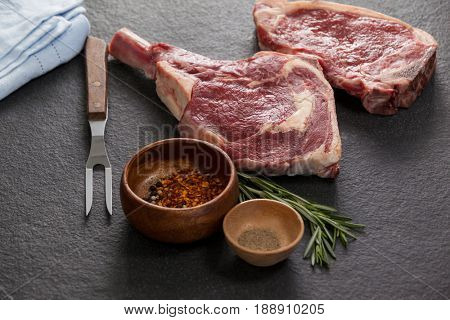 Rib chop, sirloin chop and ingredients against black background