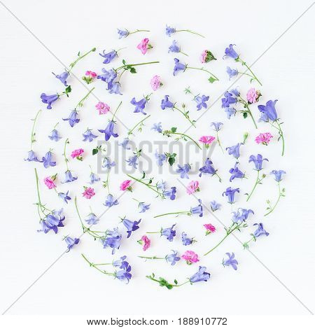 Pattern made of bellflower pansy flowers and pink flowers on white background. Flat lay top view