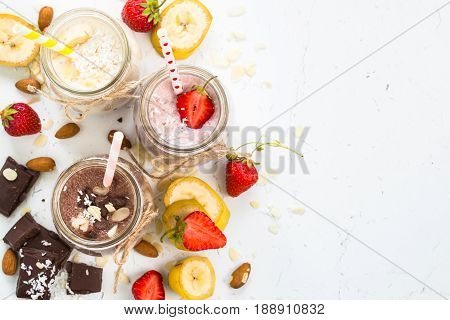 Set of milkshake in jars. Banana chocolate and strawberry milkshakes with nuts and coconut. Summer dessert. Healthy food. Top view copy space.