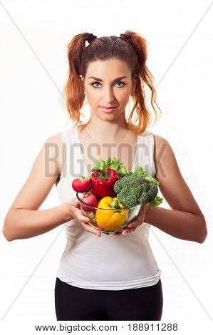 Redheaded caucasian girl holding glasses bowl with fres sweet peppers, radish, broccoli and lettuce. Vegeterian harmonic nutrition. Isolated on white background