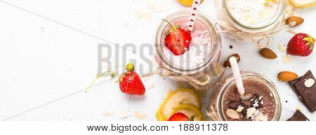 Set of milkshake in jars. Banana chocolate and strawberry milkshakes with nuts and coconut. Long banner format.
