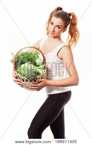 Beuatiful slim girl holding basket of fresh raw green vegetables on white background. Fitness concept. Isolated.