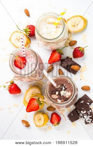 Set of milkshake in jars. Banana chocolate and strawberry milkshakes with nuts and coconut. Summer dessert. Healthy food. Top view on white table.
