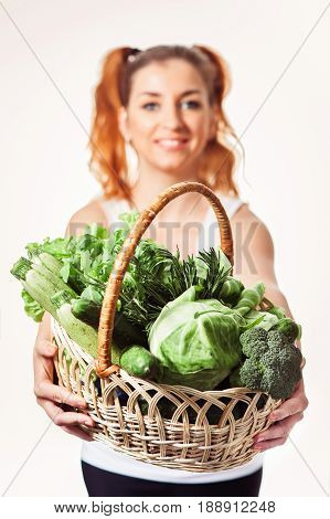 Beuatiful smiling girl holding basket of fresh raw green vegetables isolated. Vegan nutrition. Low-Caloric diet. Selective focus.