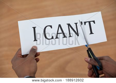 Conceptual image of businessman cutting a paper that reads we cant on white background