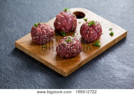 Minced beef garnished with coriander leaves on wooden board against black background