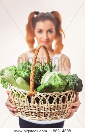 Beuatiful caucasian girl holding basket of fresh raw green vegetables isolated. Vegan nutrition. Low-Caloric diet. Selective focus.